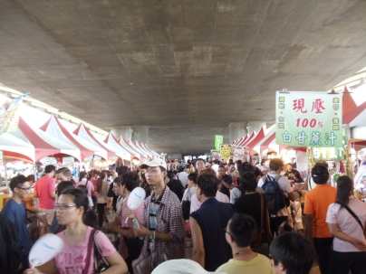 Market in cool shade of overpass